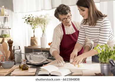 Grandmother teaching her granddaughter baking cake, reading recipe from book