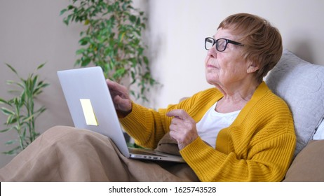 Grandmother Using Laptop Computer Relaxing In Bed. Computing Services for Retirees.
