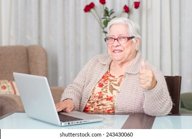 Grandmother using laptop at home. showing hand ok sign