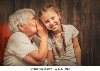 grandmother whispers in her ear to the granddaughter, time with loved ones