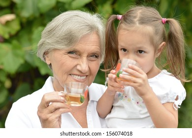 Grandmother wid little girl standing together outdoors holding cups