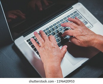 Grandmother works behind laptop, typing on keyboard with her old hands with wrinkles. Modern old pensioner working from home. Close up view of elderly woman's hands