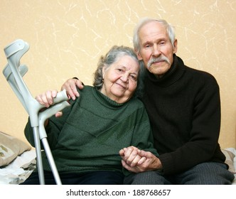 Grandpa in a dark sweater gently embracing grandmother who keeps him at arm crutches