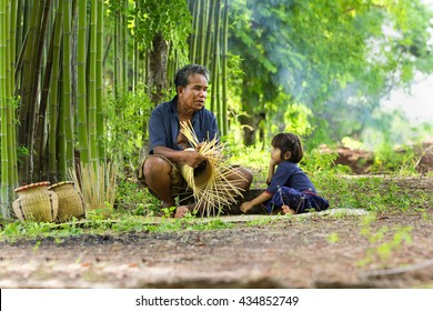 Grandpa is doing a storyteller to his granddaughter during weaving the bamboo basket.