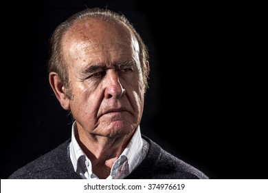 Grandpa gets serious. Old man looks with angry face, on black background