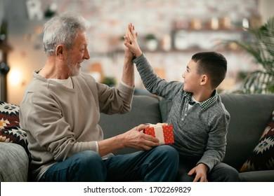 Grandpa giving his grandson birthday gift. Grandfather becomes present from grandchild.