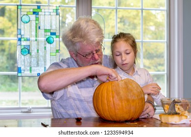 grandpa and grand daughter scoop out the insides of an orange pumpkin for a Halloween decoration