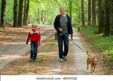 Grandpa and grandchild are walking the dog in the forest