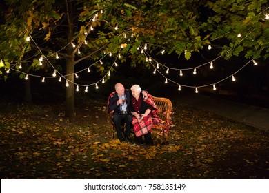 Grandpa and grandma drink tea in the Park.