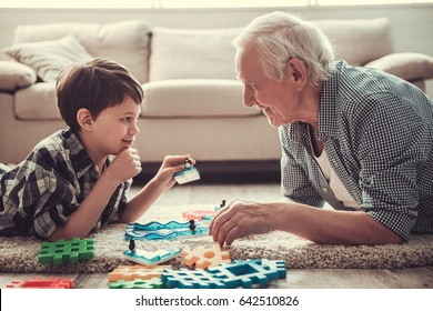 Grandpa and grandson are playing with toys, looking at each other and smiling while resting together at home