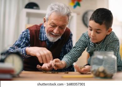 Grandpa and grandson saving money. Grandfather teaching grandchild how to save money.