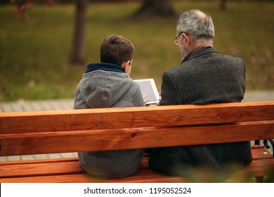 Grandpa and grandson seat on the bench and use a tablet