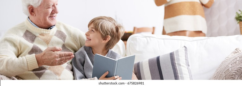 Grandpa and happy grandson sitting on a sofa, talking and reading