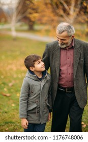 Grandpa and his grandson are walking in the park. The spend time together