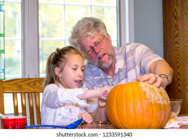 Grandpa listens as his granddaughter describes just exactly the vision she has for a jack o lantern face