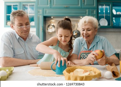 Grandpa looks how granddaughter and granny baking an apple pie. Family harmony and golden years.
