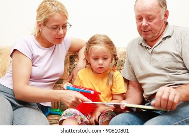 Grandpa, mother and grand-daughter reading and playing