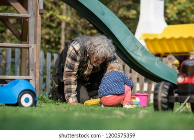 Grandpa playing with his granddaughter outside in backyard as they sit on the grass under a slide and play with sand toys and buckets.