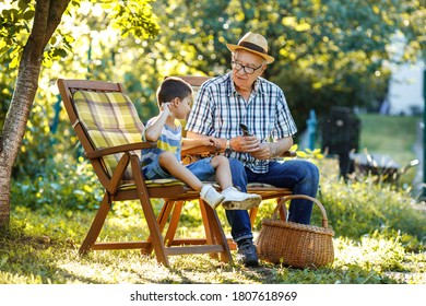 Grandpa sitting with his grandson in the garden.They talking and enjoying in beautiful summer day.