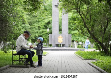 Grandpa is walking with her grandson in a spring park. Grandson and grandfather on walk. Grandpa is talking to a little boy.