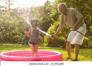 Grandparent and grandchild playing outdoor with hose