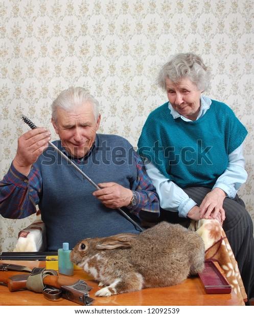 grandparent and rabbit prepare double-barreled gun to hunt