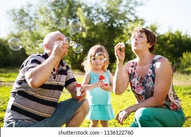 grandparents blowing soap bubbles to grandchild