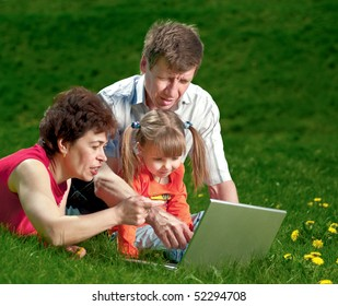 Grandparents with child sit in grass and look at laptop