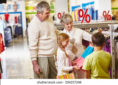 Grandparents choosing new clothes for granddaughter and grandson