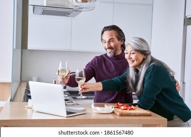 Großeltern, die mit Enkelkindern kommunizieren, können über einen Videochat auf dem Computer von zu Hause aus in der modernen Küche mit Weißwein trinken und Gläser auf den Bildschirm ziehen