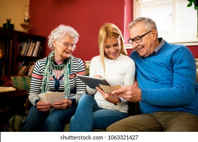 Grandparents compare photos from youth with digital photos from granddaughter and having great time together