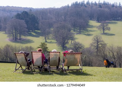 Grandparents day out. Pensioners on vacation in the countryside. Four elderly people sitting on deckchairs admiring a stunning English country landscape. Grandchild pushchair in the distance.