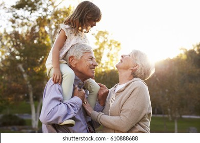 Grandparents Giving Granddaughter A Shoulder Ride In Park