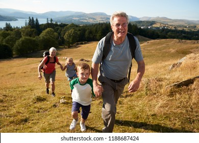 Grandparents With Grandchildren Climbing Hill On Hike Through Countryside In Lake District UK Together