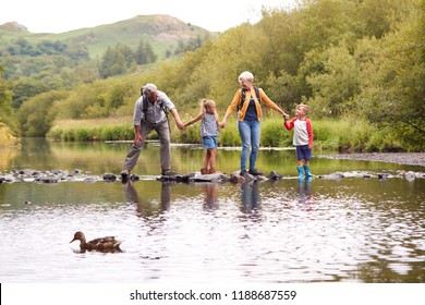 Grandparents With Grandchildren Crossing River Whilst Hiking In UK Lake District