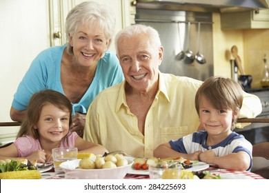Grandparents And Grandchildren Eating Meal Together In Kitchen