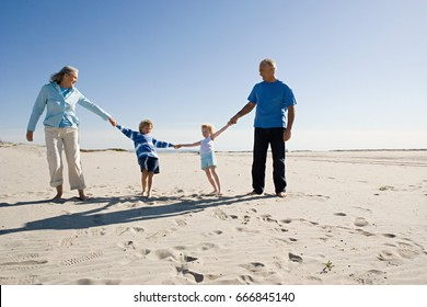 Grandparents and grandchildren holding hands, walking on beach