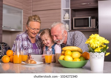 Grandparents with grandchildren in the kitchen preparing meal and having fun