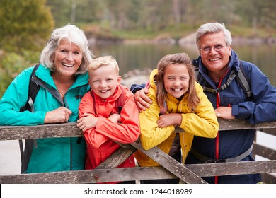 Grandparents and grandchildren leaning on a wooden fence in the countryside laughing, Lake District, UK