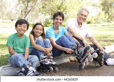 Grandparents With Grandchildren Putting On In Line Skates In Park
