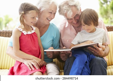 Grandparents And Grandchildren Reading Book On Garden Seat