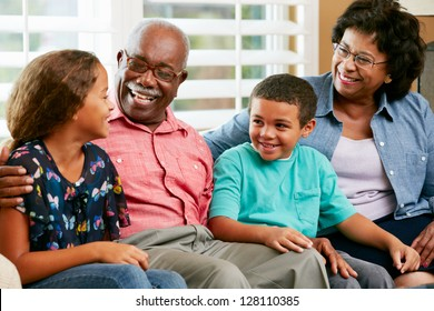 Grandparents With Grandchildren Sitting On Sofa And Talking