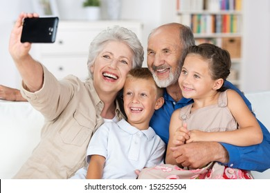 Grandparents and grandchildren sitting together in a close group on a sofa laughing and doing a self portrait with a hand held camera on a mobile phone
