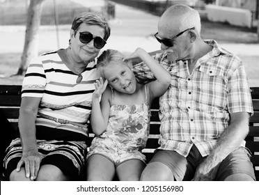 Grandparents And Granddaughter Enjoying Day In Park