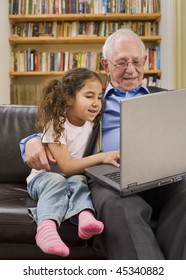 grandparents and granddaughter with laptop computer at home