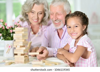grandparents and granddaughter playing with wooden blocks