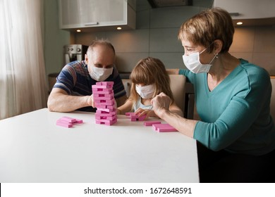 grandparents with granddaughter wearing medical face mask playing  board game together at home. quarantine. health concept. Corona Virus.