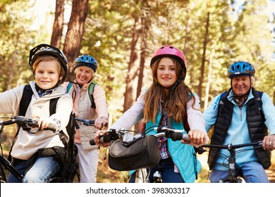 Grandparents and grandkids cycling on forest trail, close up