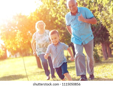 Grandparents with grandson enjoying time together in park.