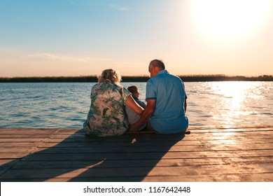 Grandparents with grandson enjoying time together by the lake. They sitting on pier.